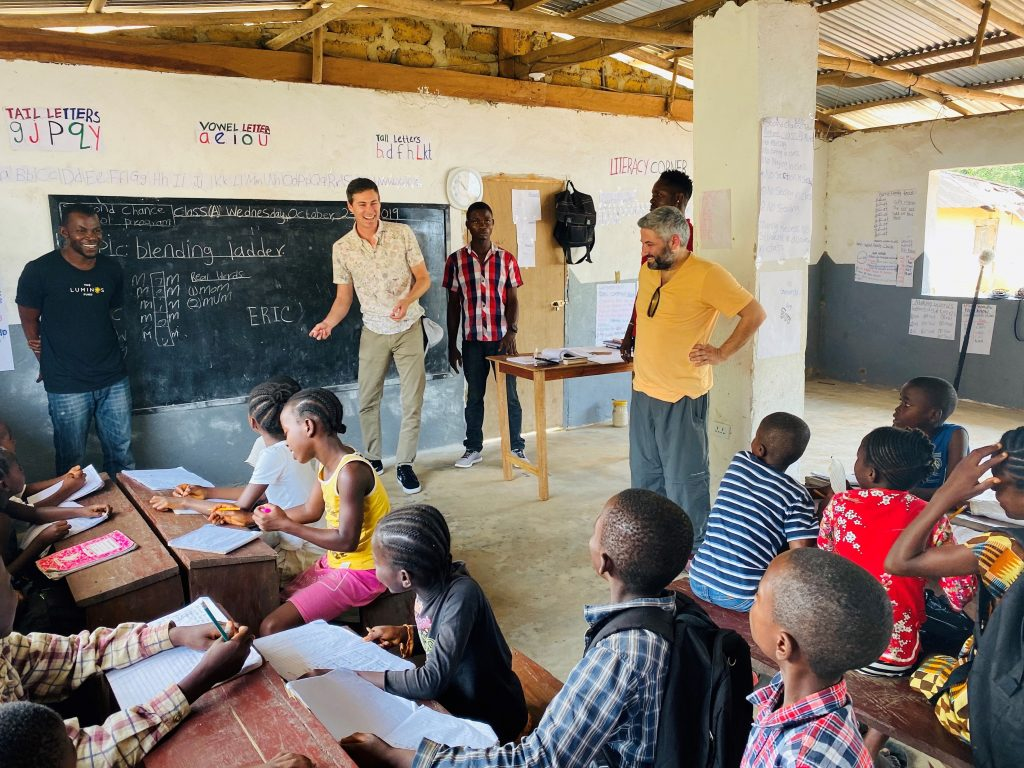 Abba, left, guides a classroom visit in Bomi County with friends of the Luminos Fund in October 2019