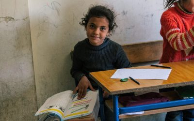 Before the pandemic, a refugee girl studies at a school in Lebanon supported by the Luminos Fund.