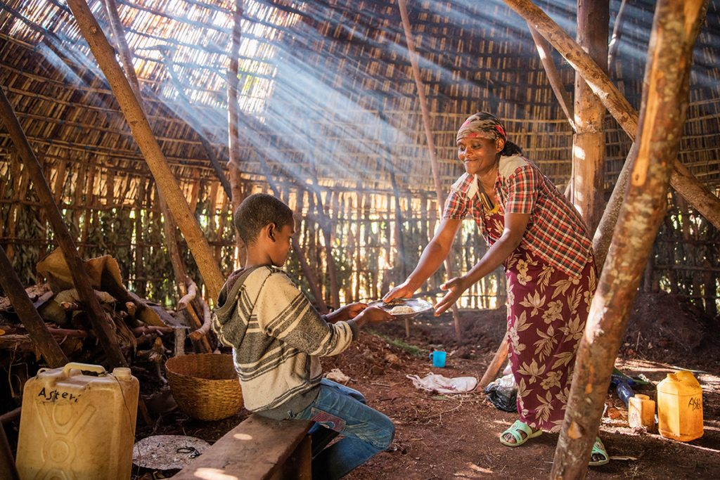 Inside their home, Anteneh's mother, Aster, prepares a wheat porridge called kinche for breakfast.