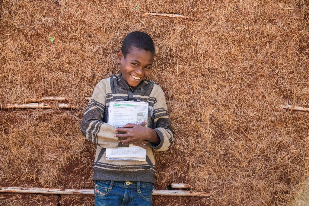 Anteneh smiles outside his home, holding school books and his notebook.
